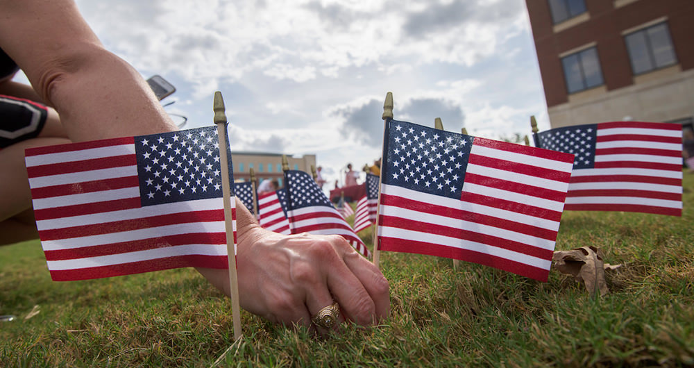 A hand placing small American flags in the ground